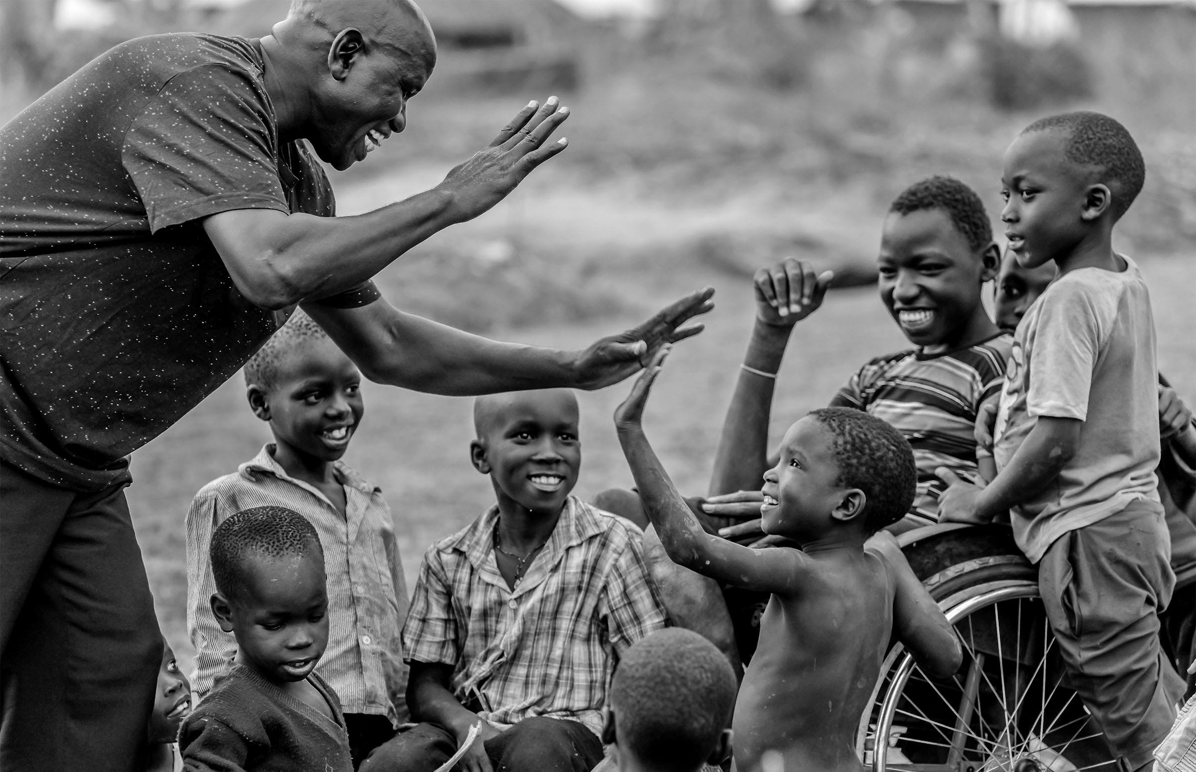 a man high fives children in the setting of a refugee camp