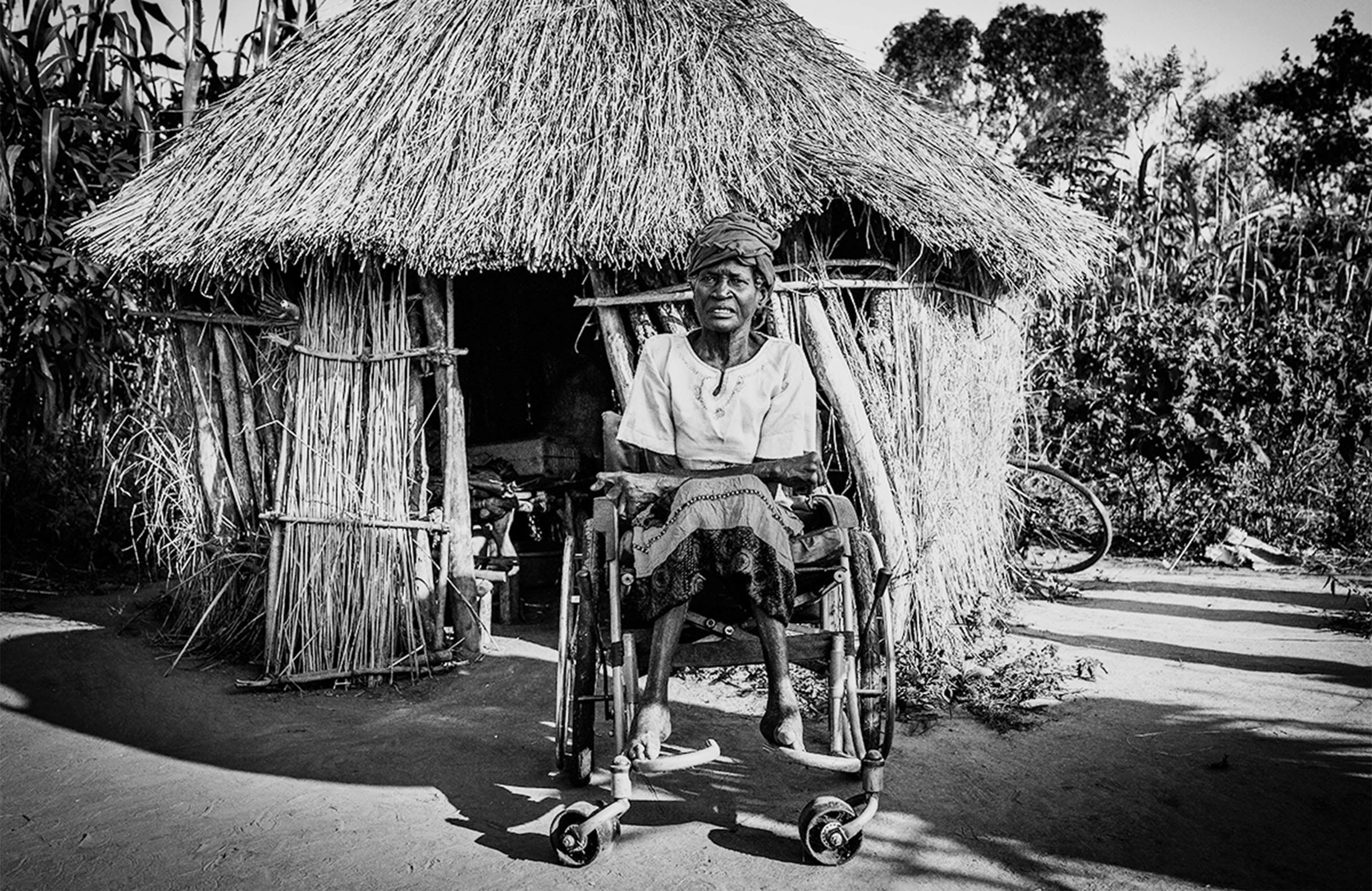 An elderly woman in a wheelchair outside a mud hut, looks back at the camera