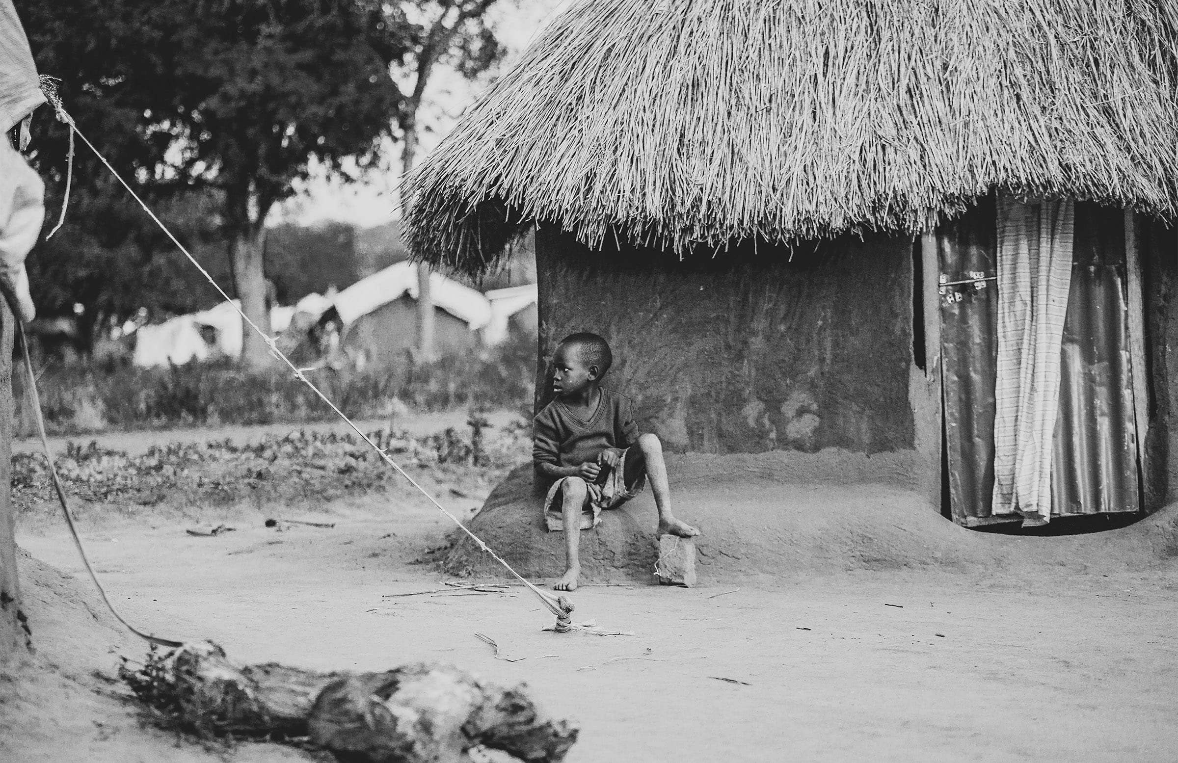 A young boy sits outside a mud hut, with his foot on a brick