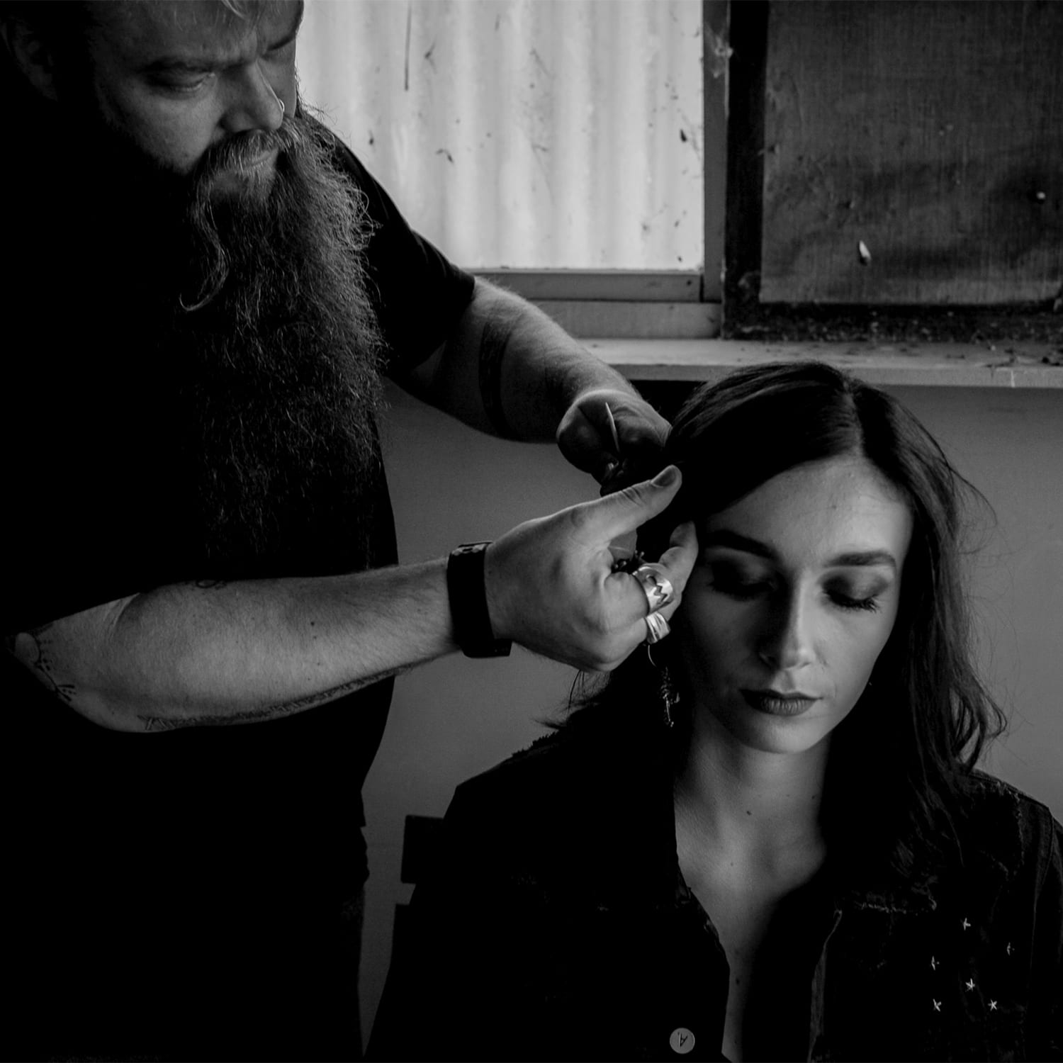 a man works on a young woman's hair as she is sitting