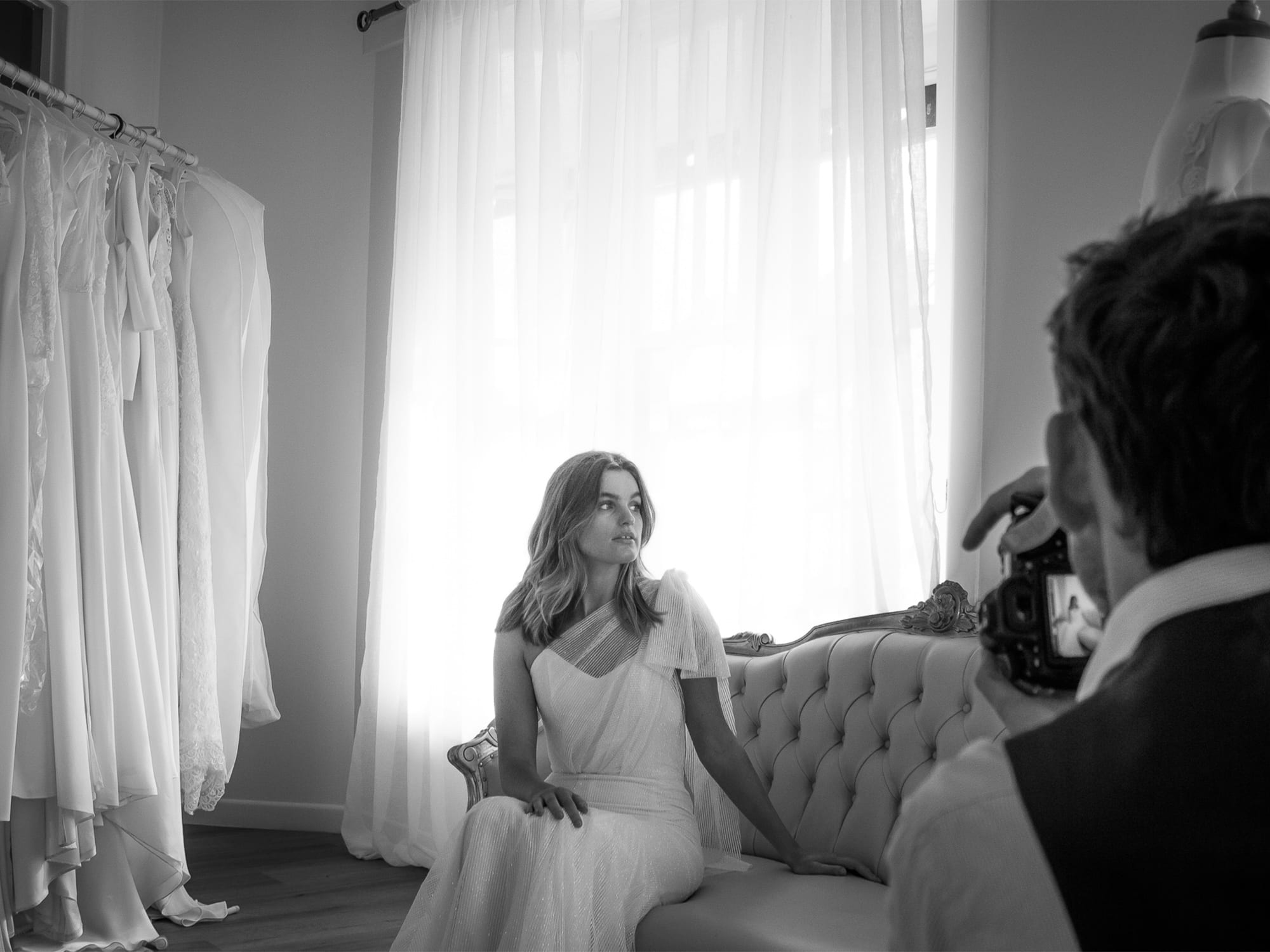 a woman in a white wedding gown sits on a sofa as a man takes a photo