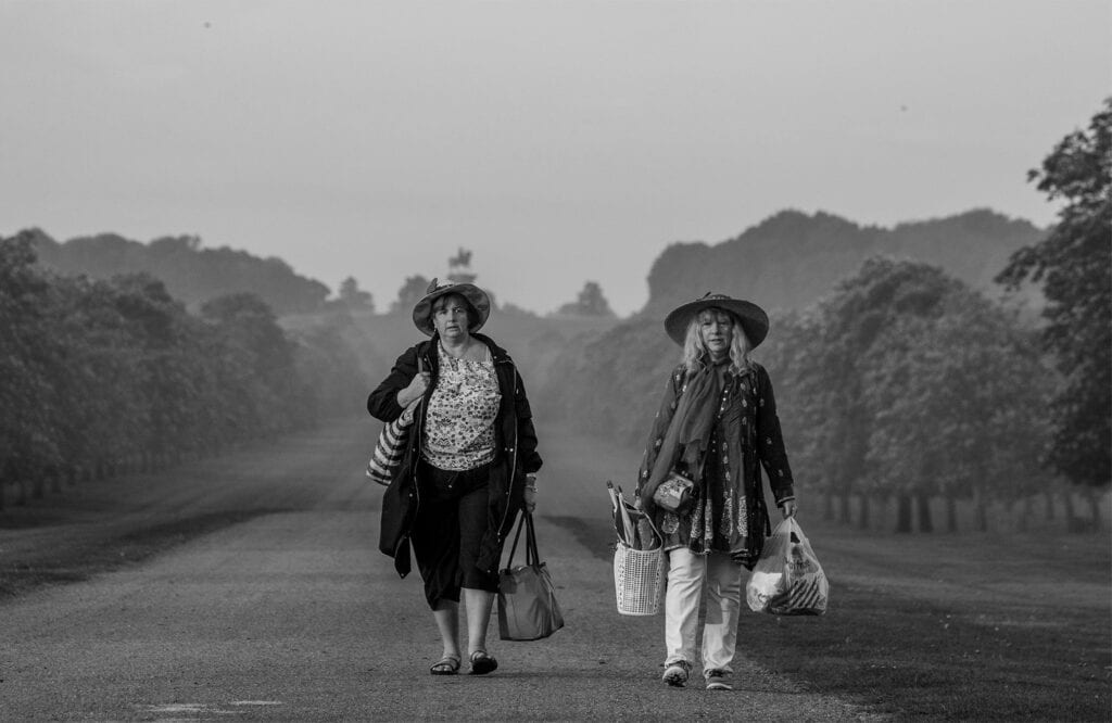 two women carrying shopping bags walk along a path in the countryside with trees either side