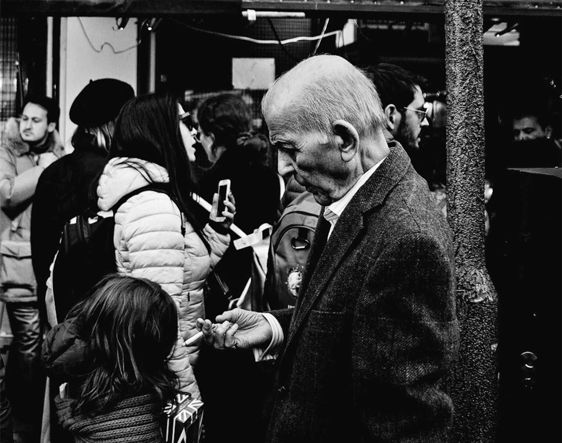 a man standing outside a shop looks down at the cigarette in his hand