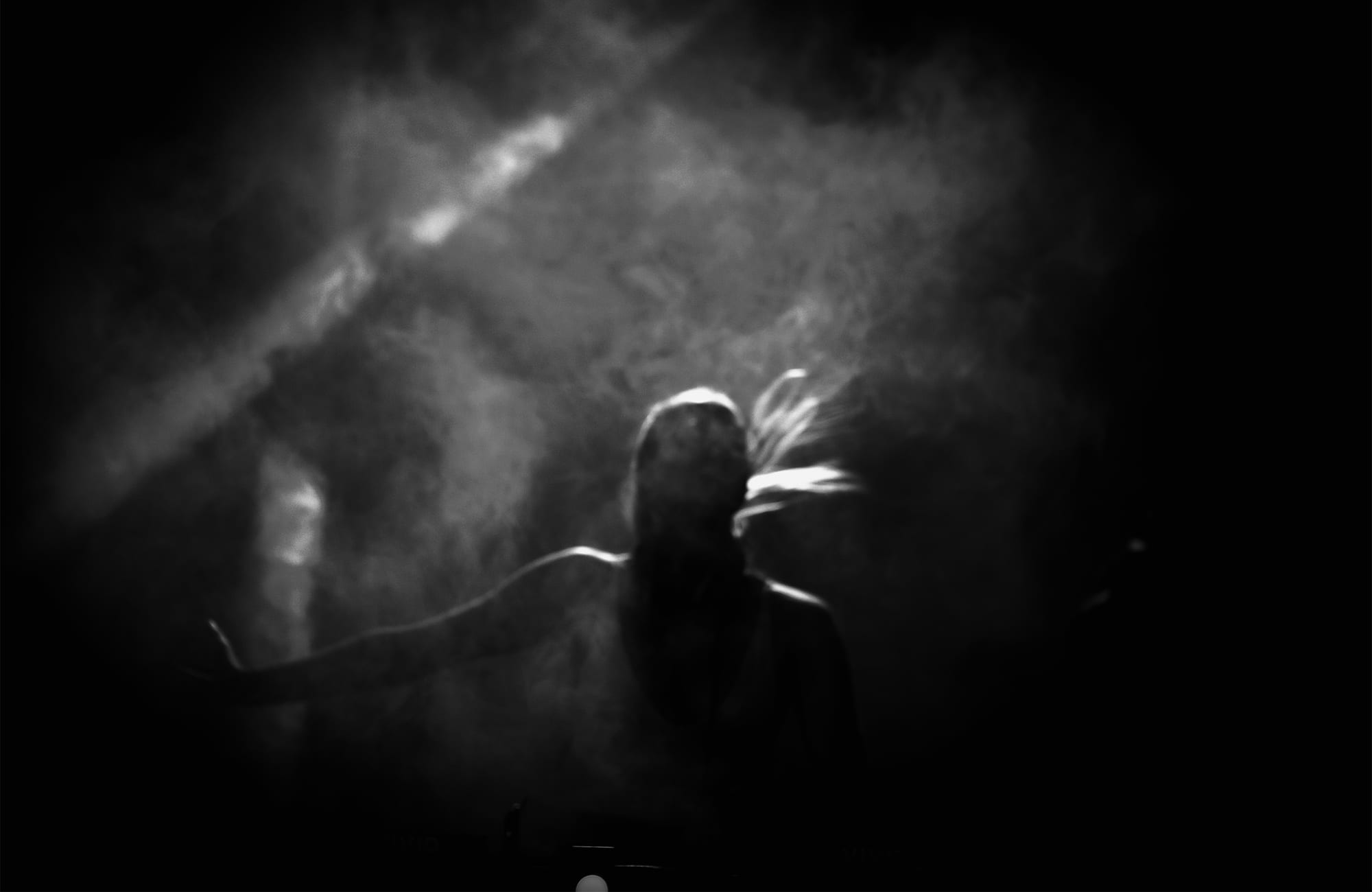 a woman in near darkness with her hair blowing around