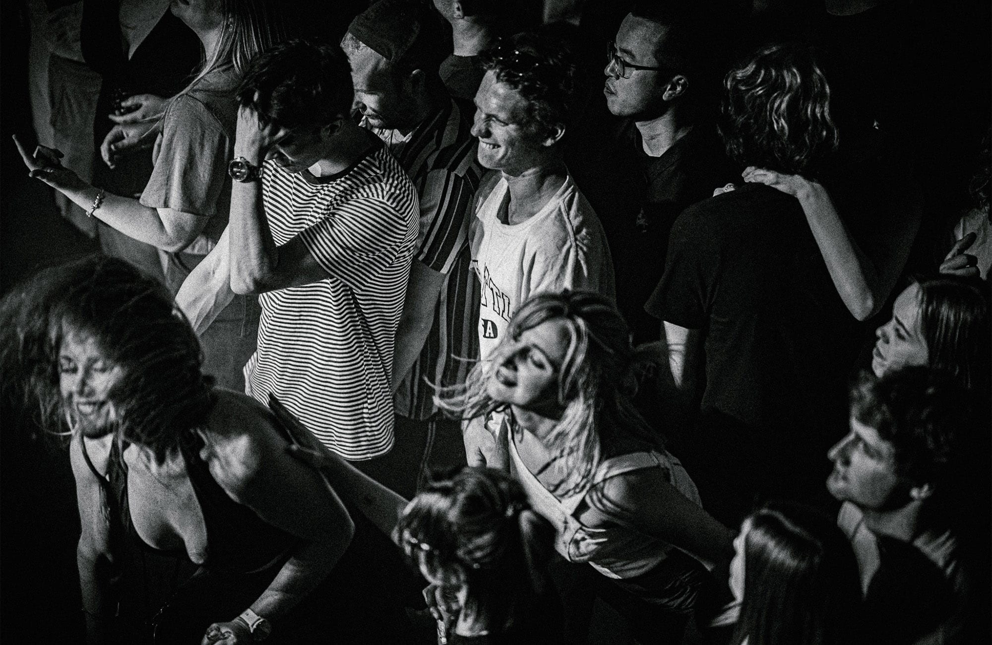 people dance and sing in a crowd at a nightclub