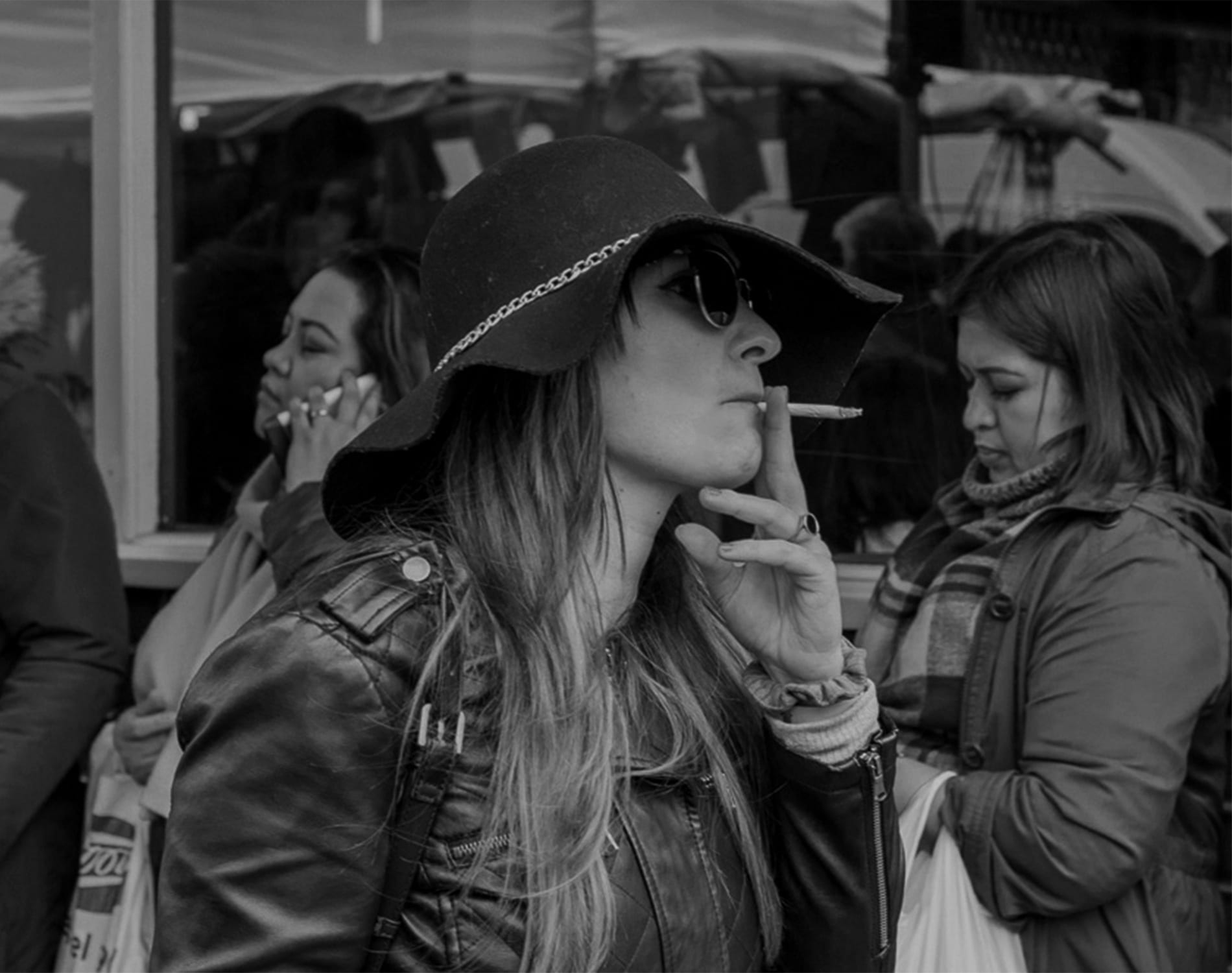 a woman in a floppy hat smokes as she walks down a busy street