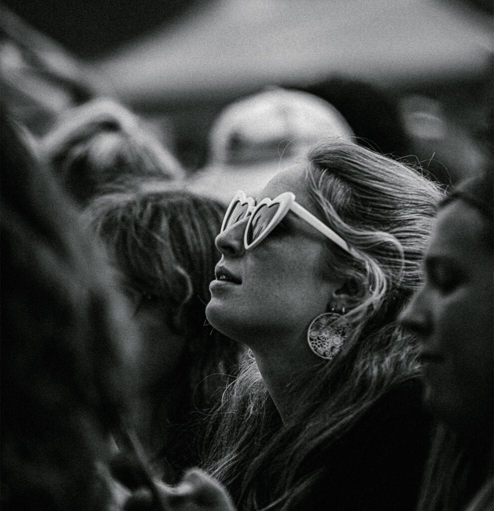 a young woman wearing retro sunglasses listens to music outside