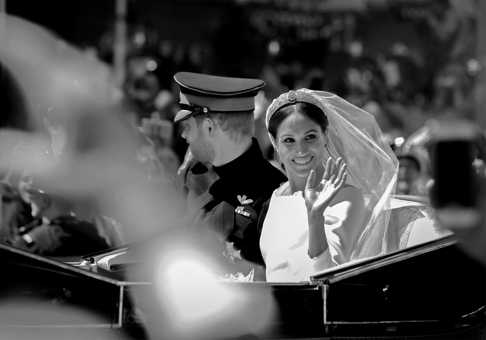 a bride sitting in a carriage next to her groom waves and smiles as people on the street