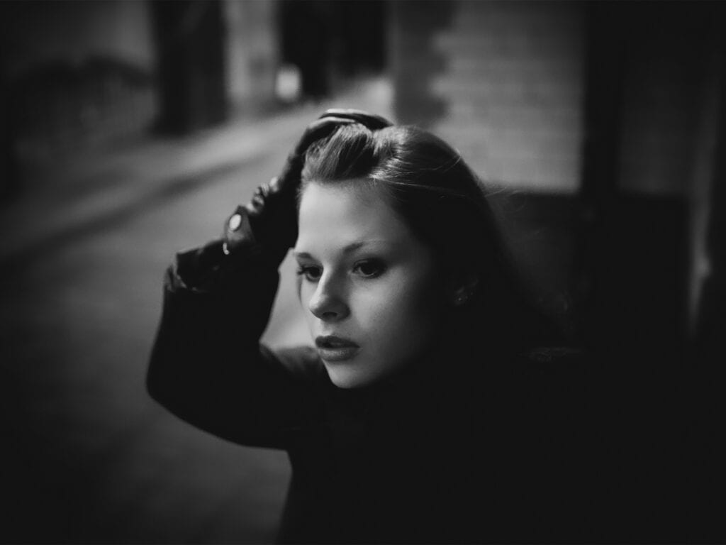 a woman in a dark alley holds her hair back