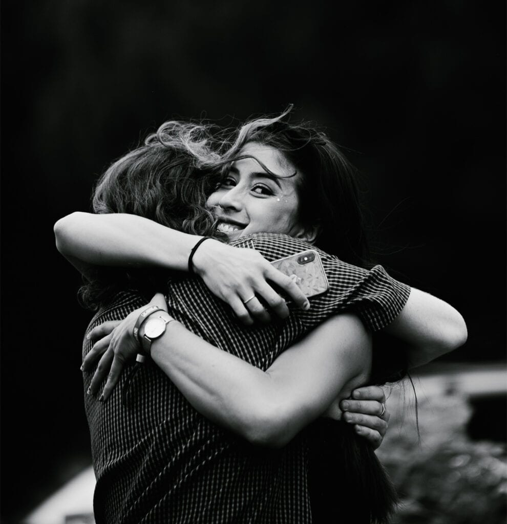 two young women hug outside, with one smiling at the camera